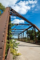 Rural one lane iron bridge with blue sky and puffy clouds in the American Midwest