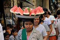 Melon seller transporting a bowl on her head at a street market in the historic centre of Yangon, Rangoon, Myanmar, Burma, Southeast Asia, Asia