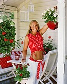 Woman at patio hanging potted flowers and looking at camera