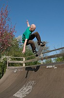 Skateboarder jumping at the top of a half_pipe