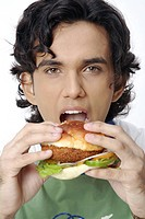 Teenage boy holding burger in both hand showing eating expression MR 687T