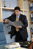 Executive holding file in both hand looking and reading it standing in cabin MR 687U