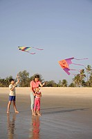 South Asian Indian mother and children trying to fly colourful kites on seashore , Shiroda , Dist Sindhudurga , Maharashtra , India MR703D,703E,703F,7...