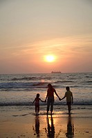 South Asian Indian mother holding hands of children looking at golden sunset on seashore , Shiroda , Dist Sindhudurga , Maharashtra , India MR 703E,70...