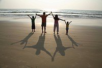 South Asian Indian parent and children holding hands facing sun with long shadows behind them on sand at seashore , Shiroda , Dist Sindhudurga, Mahara...
