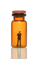 Pensive miniature business man figure in a glass pill bottle, symbolic image for the pharmacy business