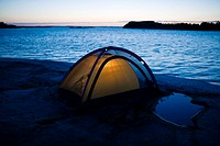 Illuminated tent by sea at dusk