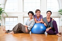 Portrait of three women with fitness ball in gym