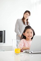 Girl using laptop and mother watching her