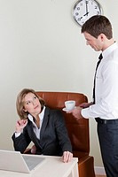 Female manager having coffee served by his male colleague