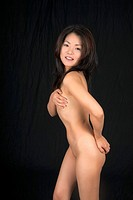Beautiful and sexy Asian woman posing for a nude figure study on a black background