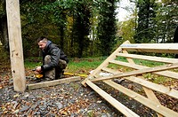 Man drilling holes for gate hinges in a timber post, with a cordless electric drill, Wales