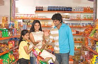 Parents with daughter standing with trolley in supermarket MR748A,748B,748D