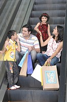 Parents carrying colourful bags with kids standing on escalator in shopping mall MR748E,748F, 748G,748H