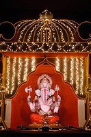 Idol of lord Ganesh elephant headed god kept in gaily decorated frame of illuminated lights , Ganpati festival at Pune , Maharashtra , India