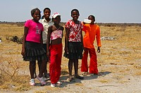 Group of curious African girls at the age of 12 to 14 years wearing European clothing in the steppe near Rakops, Republic of Botswana, Africa