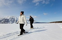 Young woman snow-shoeing, hiking with snow shoes, on frozen Kathleen Lake, man, St. Elias Mountains behind, Kluane National Park and Reserve, Yukon Te...