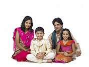 South Asian Indian family with father mother son and daughter sitting smiling and looking at camera MR 698 , 699 , 700 , 701
