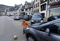 Child running onto the street after a ball, Kobern, Rhineland-Palatinate, Germany, Europe