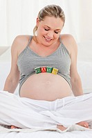 Pregnant woman with baby cubes on her belly at home