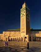 Moroccan man and women walking on the plaza of the Hassan II Mosque Casablanca at sunset, Morocco