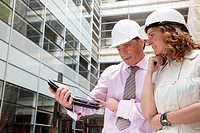 Architect and client with tablet PC in construction site