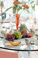 Fruit buffet on a stylish laid table in a luxuriously furnished dining room with modern design and an elegant table setting
