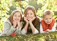 Group Of 3 Children Realxing Outdoors In Autumn Landscape