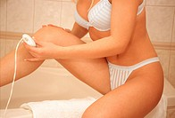 Woman in the bath shaves the legs