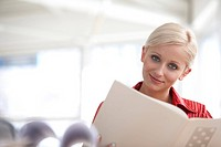 portrait of young blonde businesswoman reading document