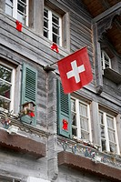 swiss flag hanging on house facade in Brienz in Switzerland