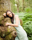 portrait of young woman leaning against tree