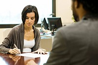 Woman signing document in office