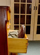 man's legs and shoes lying down in open dresser drawer