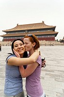 Tourist kissing her friend in front of the Hall for Worship Of Ancestors, The Forbidden City, Beijing, China, Asia  MR