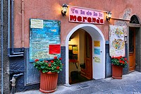 Colorful menus and signs outside of a restaurant in the village of Manarola in the Cinque Terre region of Italy
