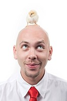 Portrait of cheerful man with cute yellow chick on his bald head
