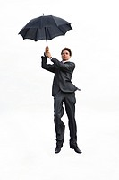 Image of businessman holding umbrella and flying on a white background
