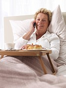 Woman on cell phone having breakfast in bed