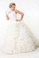 Image of elegant bride in fashionable white wedding gown posing before camera