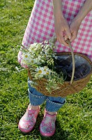 Woman wearing apron holding basket with flowers