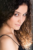 Close_up of beautiful brunette with perm looking at camera with smile