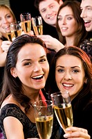Two young charming women clink glasses at a evening_party