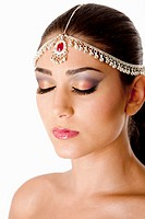 Beautiful face of a Middle Eastern woman with Arabic style makeup and head jewelry, typacally used by Indian belly dancers, isolated