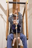 Grandfather and toddler grandson sit together and lift themselves with a rope and pulley system at the Imaginarium, Anchorage Museum at the Rasmuson C...