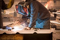 View of welder working on a steel fabrictaion structure at Steelfab in Anchorage, Southcentral Alaska, Winter