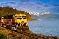 An Alaska Railroad passenger train rounds a corner along Turnagain Arm near Bird Creek, Southcentral Alaska, Summer