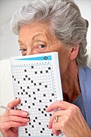 senior woman in a mauve cardigan, holding a crosswords magazine in front of her at home