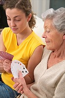senior woman in beige playing cards with a young woman at home