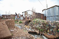 people crossing river of sewage, Kibera Kenya